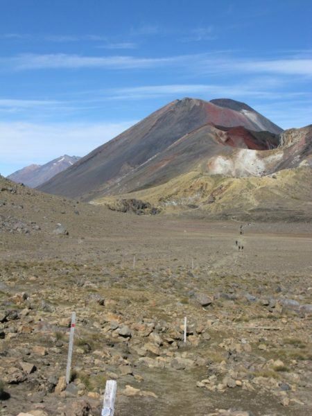Our first glimpse of Mount Doom on the Tongariro crossing, with people walking along the trail in the distance