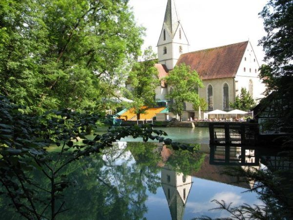 reflections of a church in a blue pond in Germany