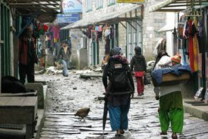 Backpackers walking through Lukla Nepal, talking about what makes you a traveler