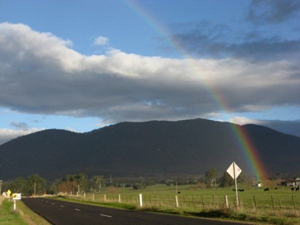 Rainbow over mountain background with black road in Rubicon Australia