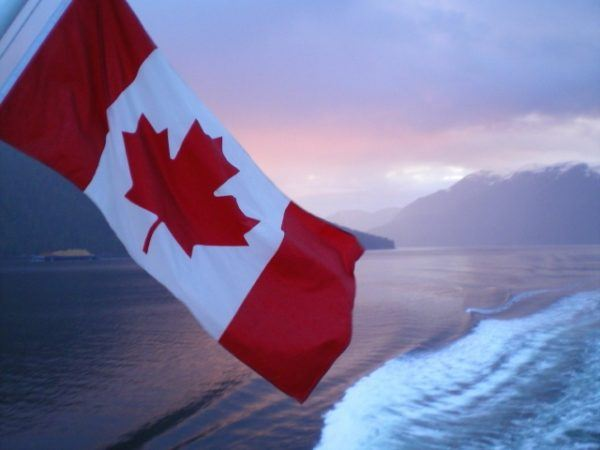 Canadian flag against sunset and water