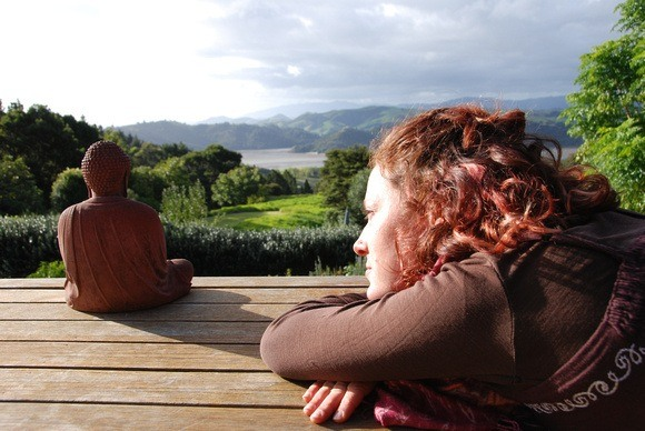 Nora Dunn, The Professional Hobo, chillin with a buddha at Mana Retreat Centre in Coromandel, New Zealand