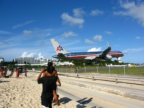 an American Airlines airplane just clears the beach at the end of the runway in St Martin