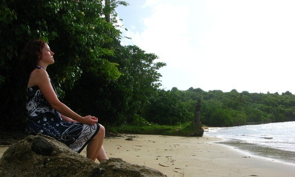 Nora Dunn, The Professional Hobo, meditating on a beach while spending three months in Grenada