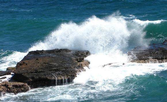 ocean wave crashing over rocks