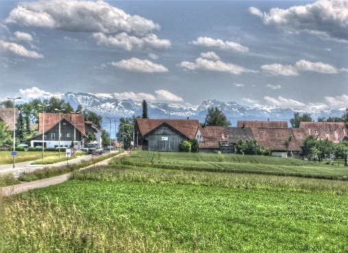 peaceful mountains of Switzerland with farmland in foreground