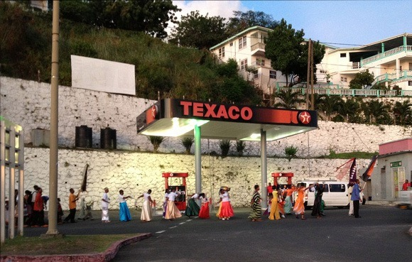 Colourful Grenada - people Parading in front of Texaco