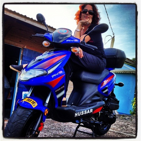 Nora Dunn on a blue scooter in Grenada