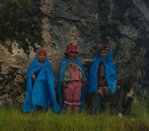 Peruvian children wearing blue tarps in the rain