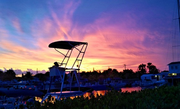 colourful sunset with a boat fishing tower