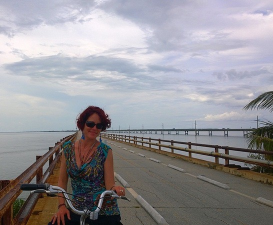 Nora Dunn, The Professional Hobo, on a bicycle by an abandoned bridge road