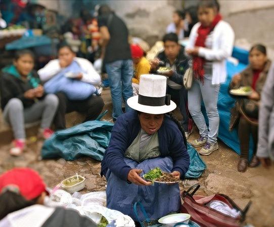 Peruvian woman serving street food in Barratio Market Cusco