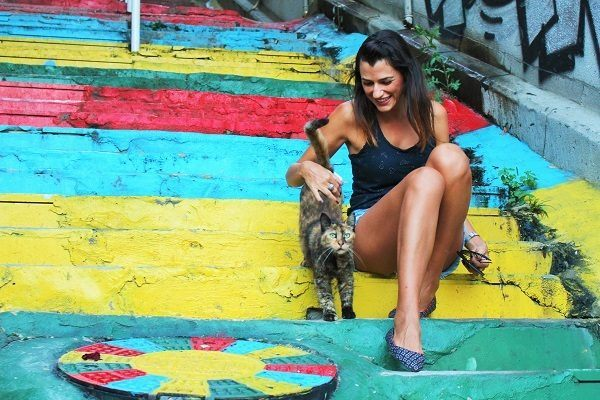 Nat of Love and road sitting on a colourful staircase petting a cat