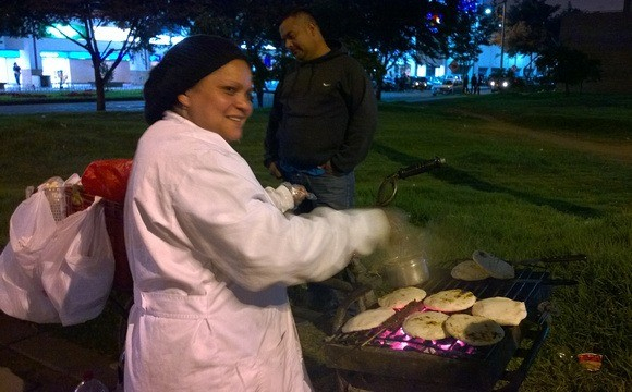 Fast food in Colombia includes arepas, seen here being made on the side of the street