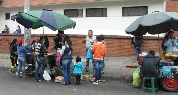 Fast food Colombia Street stands in Bogota with umbrellas