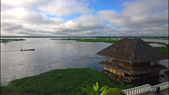 Hut on the banks of the Amazon river with a boat going by