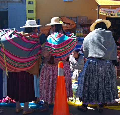 3 ladies buying fabric in the marketplace between the border of Peru and Bolivia