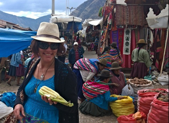 The Professional Hobo, Nora Dunn, at Pisac Market holding choclo con queso