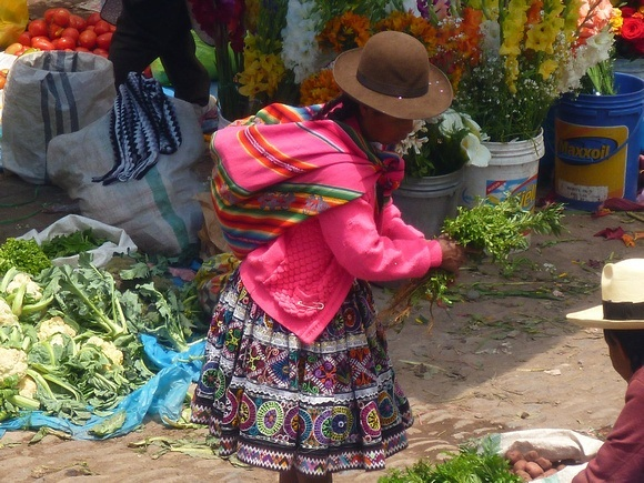 Andean woman with colourful clothing and bowler hat at a fresh market in Pisac