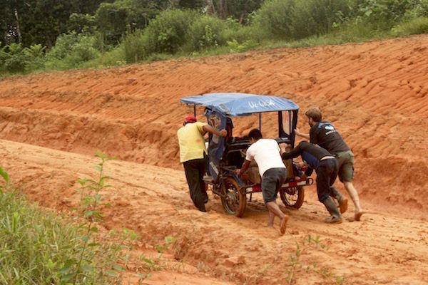 Ryan helping push a mototaxi stuck in the mud - Amazon Jungle, Peru