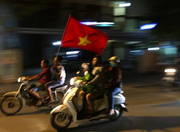 carrying the Vietnamese flag on a motorcycle