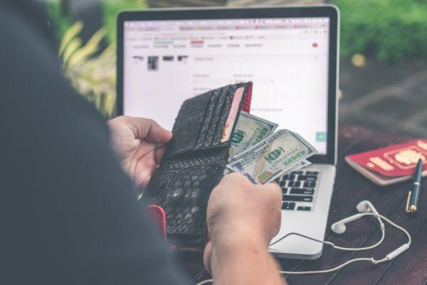 Man holding wallet and cash, sitting at his laptop - travel prep costs