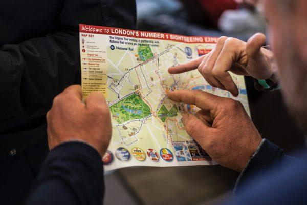 People pointing at London tour map - hidden travel costs