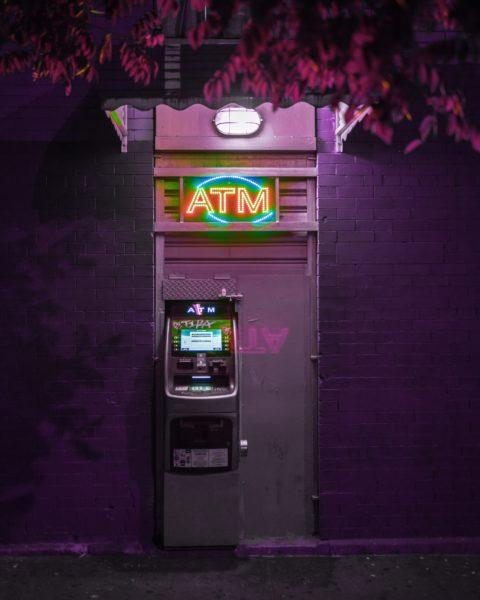 An ATM at night - how to avoid currency conversion fees while traveling