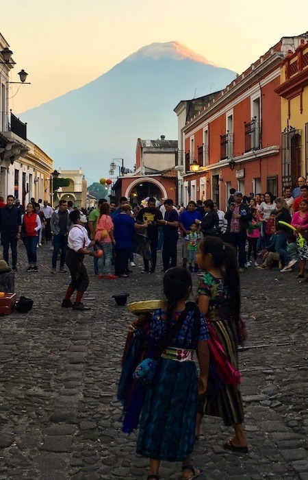 Things to do in Antigua Guatemala include walking around the town centre, with vendors, buskers, and a volcano in the background