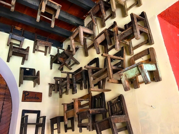 Where to stay in Antigua Guatemala? Try Posada San Sebastian, with dozens of tiny wooden chairs out front.