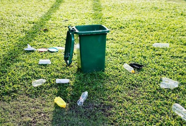 plastic bottles on a green lawn by a garbage can - this is why reusable products need to exist