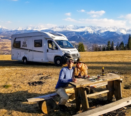 Mike and Anne Howard of HoneyTrek in the Carpathian Mountains with an RV